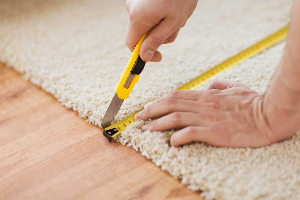 Close Up Of Male Hands Cutting Carpet With Blade